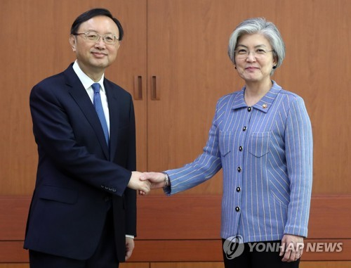 Foreign Minister Kang Kyung-wha (R) shakes hands with Chinese State Councilor Yang Jiechi before holding a meeting in Seoul on March 30, 2018. (Yonhap)