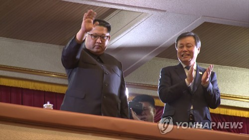 North Korean leader Kim Jong-un waves and South Korean Culture Minister Do Jong-whan claps before a South Korean art troupe holds a concert in Pyongyang in this image captured from pool footage taken