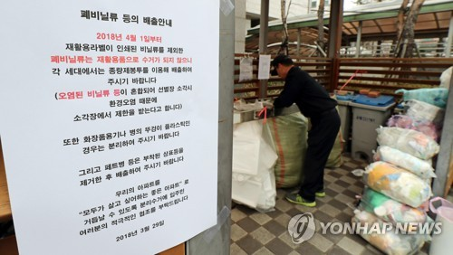 A notice announcing waste removal companies' decision not to collect plastic waste is posted on the wall of a garbage disposal area in an apartment complex in Yongsan, central Seoul, on April 1, 2018. (Yonhap)