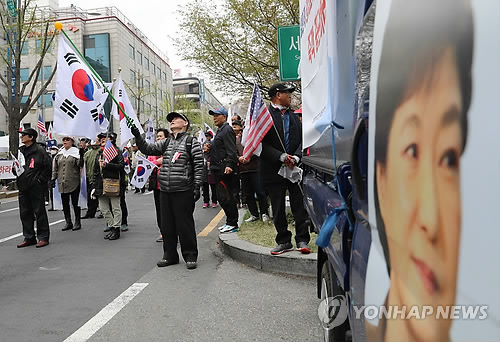 Supporters of former President Park Geun-hye wave the national flag in front of the Seoul Central District Court, before Park's sentencing trial, held in the afternoon of April 6, 2018. (Yonhap)