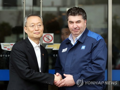 Paik Un-gyu (L), South Korean minister of trade, industry and energy, shakes hands with GM Korea President Kaher Kazem during their meeting at Bupyeong plant, west of Seoul, on April 6, 2018. (Yonhap)