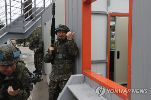 Defense ministry correspondents participate in a street gunfight using the Multiple Integrated Laser Engagement System (MILES) at the Kumgok reserve force training site in Gyeonggi Province. (Yonhap)