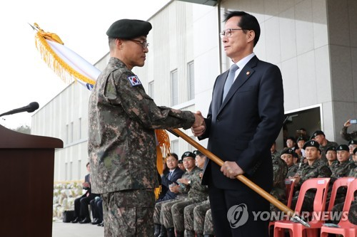 Defense Minister Song Young-moo hands over the flag of the Mobilization Force Command to its first commander Maj. Gen. Koo Won-keun during the launch ceremony of the unit in Yongin, Gyeonggi Province, on April 6, 2018. (Yonhap)