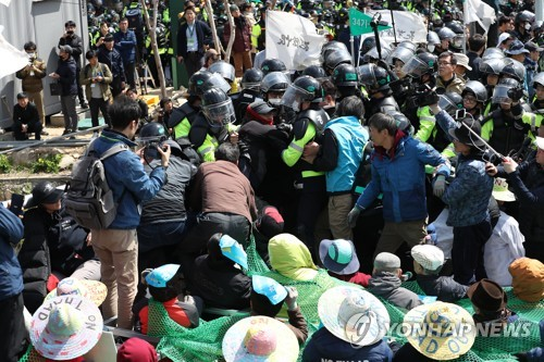Residents near the THAAD missile defense base in Sejongju, North Gyeongsang Province, clash with police on April 12, 2018, protesting against the transport of construction materials and equipment into the area. (Yonhap)