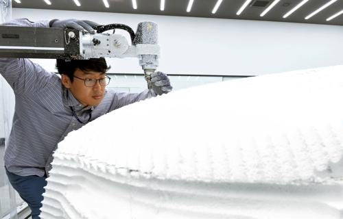 An employee of Hyundai Mobis works on a design sample for auto parts with the help of a clay model processing machine at the company's design center in Yongin, Gyeonggi Province. (Photo courtesy of Hyundai Mobis) (Yonhap)
