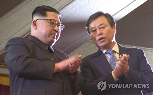 This image captured from the Joint Press Corps broadcast footage shows South Korean Culture Minister Do Jong-whan (R) speaking to North Korean leader Kim Jong-un during a South Korean music performance at East Pyongyang Grand Theatre in Pyongyang on April 1, 2018. (Yonhap)