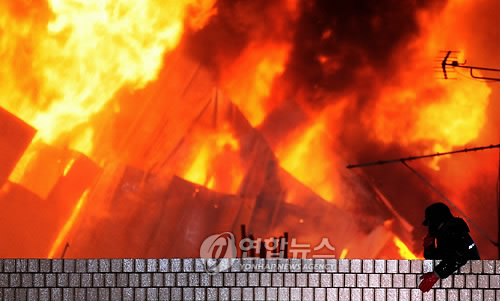 The fire pictured here claimed six lives during a police raid of a building occupied by protesters who demanded resettlement compensation in Yongsan, central Seoul, on Jan. 20, 2009. (Yonhap)