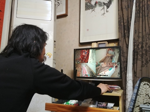 Cho Han-jeong monitors the closed-circuit cameras installed around his house on April 5, 2018. (Yonhap)
