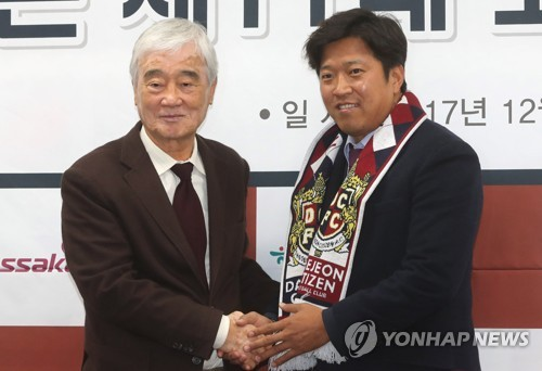 In this file photo from Dec. 1, 2017, Kim Ho (L), CEO of Daejeon Citizen football club, shakes hands with Ko Jong-soo, the team's new head coach, during Ko's inauguration ceremony at Daejeon World Cup Stadium in Daejeon, 160 kilometers south of Seoul. (Yonhap)