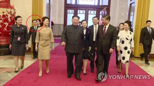 Kim Chang-son, whose face is in a red circle, accompanies Kim Jong-un on his trip to Beijing in late March in this photo released by the North's state TV broadcaster. (Yonhap) [For Use Only in the Republic of Korea. No Redistribution]