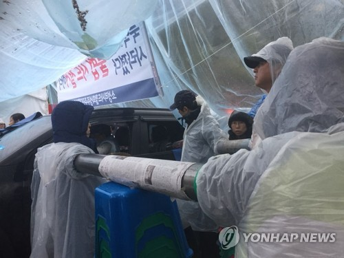 Protesters resist police by putting their arms into plastic pipes in an attempt to tie themselves together during a sit-in in Seongju, some 300 km southeast of Seoul, on April 23, 2018. (Yonhap)