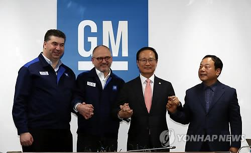 In this photo taken April 23, 2018, from left, GM Korea President and Chief Executive Kaher Kazem, GM Executive Vice President Barry Engle, ruling Democratic Party lawmaker Hong Young-pyo and Moon Seung, who represents GM Korea's 140,000 subcontractors, hold hands after the company and its union reached a tentative restructuring agreement at the main Bupyeong plant, just west of Seoul. (Yonhap)