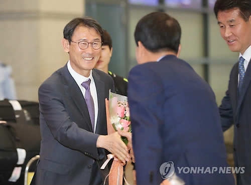 In this file photo taken April 18, 2018, South Korea women's national football team head coach Yoon Duk-yeo (L) is congratulated by Korea Football Association officials at Incheon International Airport in Incheon after his team returned home with a ticket to the 2019 FIFA Women's World Cup. (Yonhap)