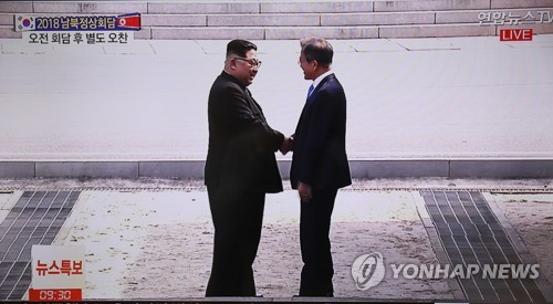 The captured image of a television broadcast shows South Korean President Moon Jae-in (R) and North Korean leader Kim Jong-un shaking hands after briefly crossing the inter-Korean border at the Joint Security Area of Panmunjom, where they met on April 27, 2018, for the third inter-Korean summit. (Yonhap)