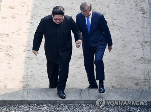 South Korean President Moon Jae-in (R) and North Korean leader Kim Jong-un cross the inter-Korean border at the Joint Security Area of Panmunjom on April 27, 2018 for a meeting with Moon that will mark the third inter-Korean summit. (Yonhap)
