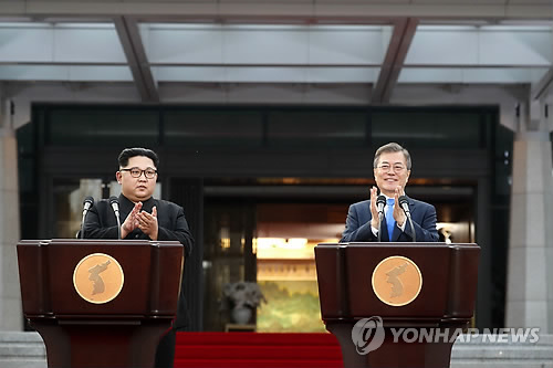 This photo, taken April 28, 2018, shows South Korean President Moon Jae-in (R) and North Korean leader Kim Jong-un issuing a joint declaration of peace and cooperation at the border truce village of Panmunjom. (Yonhap)
