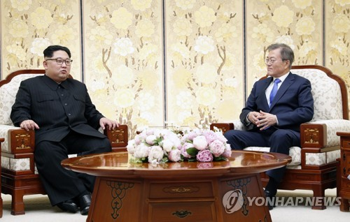 South Korean President Moon Jae-in (R) talks to North Korean leader Kim Jong-un during the historic inter-Korean summit at Peace House on the southern side of the DMZ in the truce village of Panmunjom on April 27, 2018. (Yonhap)