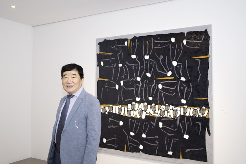 South Korean painter Hwang Young-sung poses for photos in front of his painting in Hyundai Hwarang in Seoul in this undated photo provided by the gallery. (Yonhap)