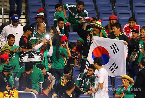 In this file photo taken Jan. 29, 2014, Mexican football fans take photos with South Korean football fans ahead of an international football friendly match between Mexico and South Korea at the Alamodome in San Antonio, United States. (Yonhap)