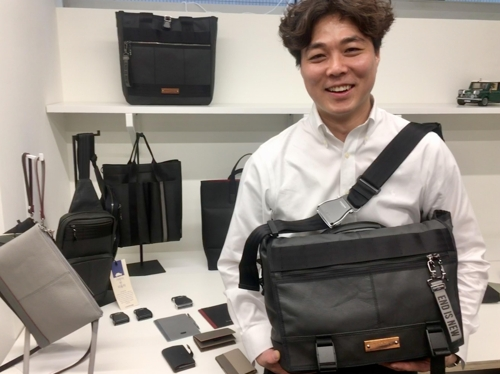 Choi Ian, head of South Korean bag maker Morethan, poses for a photo at his office in Seoul with one of the company's Continew bags made with car seat leather and a seat belt. (Yonhap)
