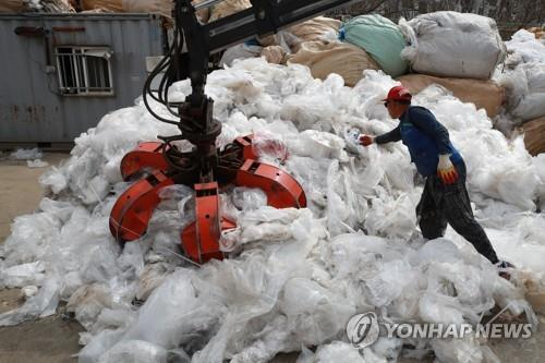 In this file photo, taken April 2, 2018, a worker at a recycling center prepares to process plastic waste in Goyang on the northwestern outskirts of Seoul. (Yonhap)