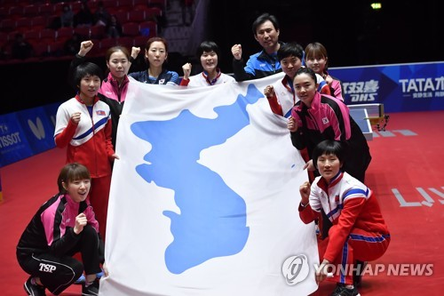 2018 members of the unified Korean women's table tennis team hold up the Korean Unification Flag after losing to Japan in the semifinals of the World Team Table Tennis Championships at Halmstad Arena in Halmstad Sweden