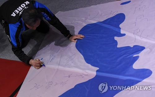 2018 South Korean women's table tennis coach An Jae-hyung signs the Korean Unification Flag after the joint Korean team lost to Japan in the semifinals of the World Team Table Tennis Championships at Halmstad Arena in H