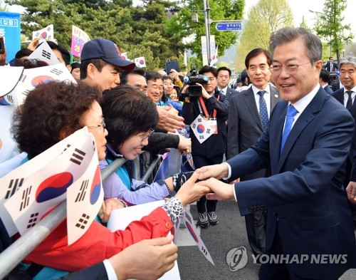 This file photo, taken April 27, 2018, shows President Moon Jae-in shaking hands with a group of people standing on the street to cheer for Moon, who was on his way to a historic summit with North Korean leader Kim Jong-un at the border truce village of Panmunjom inside the heavily-fortified Demilitarized Zone that divides the two Koreas. (Yonhap)