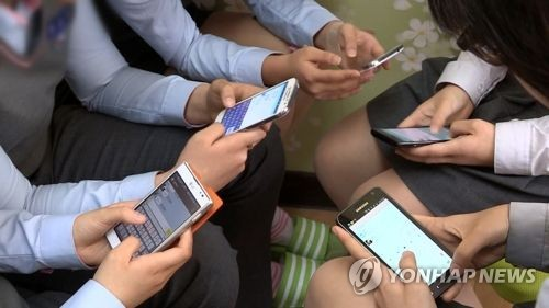 This file photo shows school kids looking at their smartphones. (Yonhap)