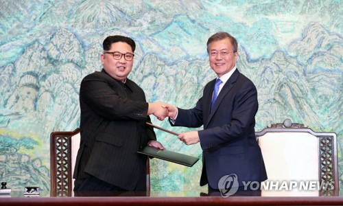 This photo, taken on April 27, 2018, shows President Moon Jae-in (R) and North Korean leader Kim Jong-un exchanging joint summit declarations that they signed after holding a summit at the border village of Panmunjom. (Yonhap)