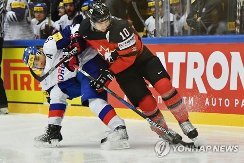 In this AFP photo taken May 6, 2018, Cho Min-ho of South Korea (L) challenges Brayden Schenn of Canada for the puck during the teams' Group B game at the International Ice Hockey Federation World Championship at Jyske Bank Boxen arena in Herning, Denmark, on May 6, 2018. (Yonhap)