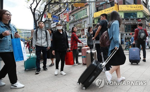 In this file photo, taken April 13, 2018, tourists walk with their luggage on Myeongdong Street in downtown Seoul. (Yonhap)