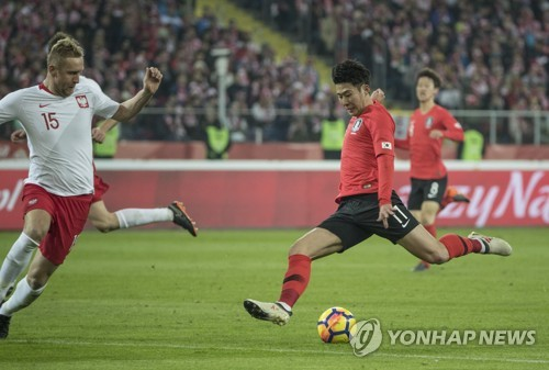 In this file photo taken on March 27, 2018, South Korea's Son Heung-min (R) takes a shot during a friendly match between South Korea and Poland in Chorzow, Poland. (Yonhap)