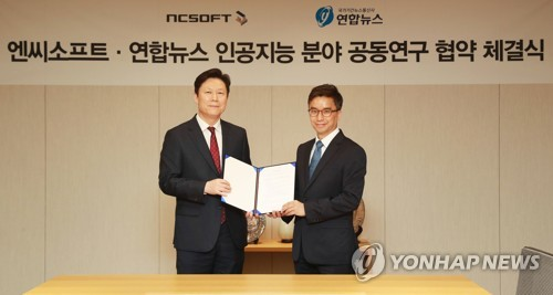 Yonhap News Agency's Managing Director for Strategic and General Affairs Lee Ki-chang (L), poses for a photo with Lee Jay-june, who heads the AI research center of NCSOFT, at Yonhap's headquarters in Seoul on May 16, 2018. (Yonhap)