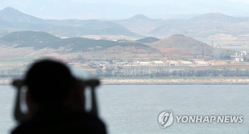 This file photo shows a South Korean tourist looking at a North Korean village through a telescope at an observation tower on Gangwha Island. (Yonhap)