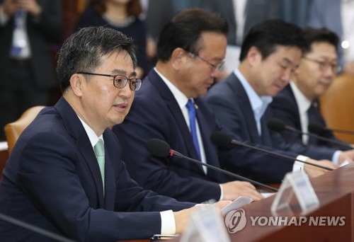 Finance Minister Kim Dong-yeon (L) outlines the government's FX intervention disclosure policy at an economy-related ministers meeting in Seoul on May 17, 2018. (Yonhap)