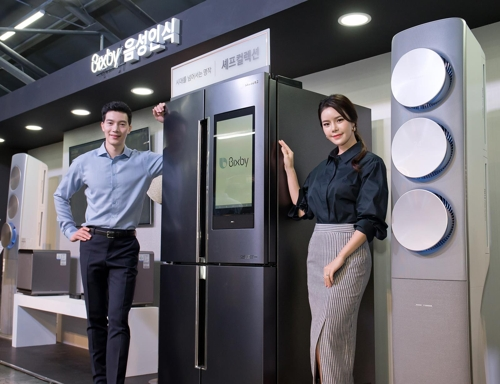 Models pose with a Samsung Electronics Co. refrigerator equipped with the voice recognition system Bixby during a press conference in Seoul in this photo released by the company on May 17, 2018. (Yonhap)