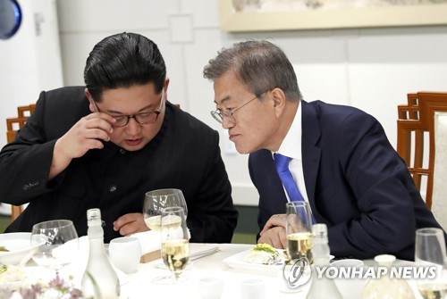 This file photo taken on April 27, 2018, shows South Korean President Moon Jae-in (R) and North Korean leader Kim Jong-un talking privately during a dinner hosted by Moon to mark their historic summit at the border village of Panmunjom. (Yonhap)