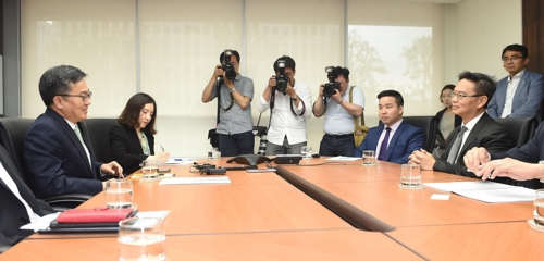 South Korean Finance Minister Kim Dong-yeon (L) speaks during a meeting with a delegation from Standard & Poor's in Seoul on May 17, 2018. (Yonhap)