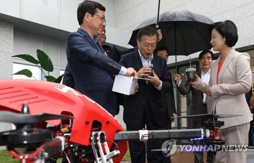 President Moon Jae-in (2nd from L) takes a sip of coffee delivered by a small, remotely controlled unmanned aerial vehicle while attending a special meeting to check the progress of his innovation-led growth strategy in Seoul on May 17, 2018. (Yonhap)