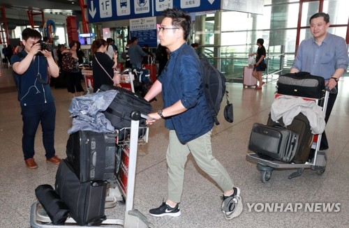 In this photo by Joint Press Corps, South Korean journalists selected to cover the dismantlement of North Korea's key nuclear test site arrive at Beijing Capital International Airport on May 21, 2018. The North said it would allow journalists from South Korea, China, Russia, the United States and Britain to report on the dismantlement between May 23-25, pending weather conditions, but the South Korean journalists's status remains in limbo with Pyongyang yet to grant them their visas. (Yonhap)