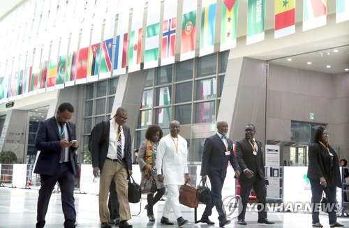 """Participants in the annual meeting of the African Development Bank (AfDB) arrive at the BEXCO convention center in Busan, some 450 km south of Seoul, on May 21, 2018, for the event's opening. More than 4,000 economic officials and business leaders from Africa and other nations will attend the five-day gathering this year, themed """"Accelerating Africa's Industrialization."""" (Yonhap)"""
