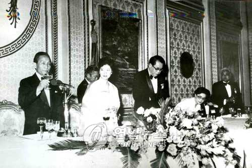 "Park Kwang-jin's ""Autumn at Bulguk Temple"" is seen behind former president Park Chung-hee (L) and his daughter Park Geun-hye, who later became president and was impeached, at the banquet hall of the state guesthouse Yeongbin-gwan on Dec. 28, 1978. (Yonhap)"
