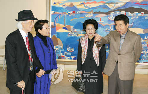 Former President Roh Moo-hyun (R) attends a solo exhibition of artist Chun Hyuck-lim at Leeyoung Contemporary Art Museum in Yongin, Gyeonggi Province, on Nov. 12, 2005. The artist is on the far left. (Yonhap)