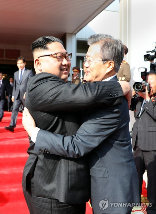 In the photo provided by South Korea's presidential office Cheong Wa Dae, North Korean leader Kim Jong-un (L) and South Korean President Moon Jae-in embrace each other before departing at the end of their surprise inter-Korean summit held at the border village of Panmunjom on May 26, 2018. (Yonhap)