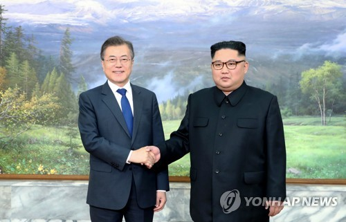 The photo, provided by South Korea's presidential office Cheong Wa Dae, shows South Korean President Moon Jae-in (L) and North Korean leader Kim Jong-un shaking hands before their second bilateral summit in less than a month held at the border village of Panmunjom on May 26, 2018. (Yonhap)