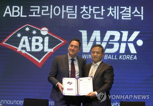 In this file photo from May 21, 2018, Cam Vale (L), CEO of the Australian Baseball League, and Kim Hyun-soo, head of Winter Ball Korea, pose with a contract for the founding of an all-South Korean club in the ABL starting in the 2018-2019 season in a ceremony in Seoul. (Yonhap)