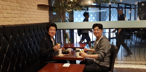 In this photo taken June 5, 2018, Banpo Riche resident Yang Jong-moon (L) and his son eat breakfast at the apartment's community center in southern Seoul. He likes to pick up breakfast there once or twice a week. (Yonhap)