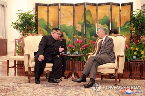 North Korean leader Kim Jong-un (L) holds talks with Singapore's Prime Minister Lee Hsien Loong in Singapore on June 10, 2018, in this photo provided by Singapore's communications and information ministry. Kim arrived in the island country earlier in the day to hold a historic summit with U.S. President Donald Trump on June 12. (Yonhap)