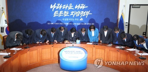 Leaders of the ruling Democratic Party, including party chief Choo Mi-ae (sixth from L), bow in a meeting held at the National Assembly in Seoul on June 14, 2018 to express their gratitude to the people over the party's landslide victory in the local and parliamentary by-elections held the previous day. (Yonhap)